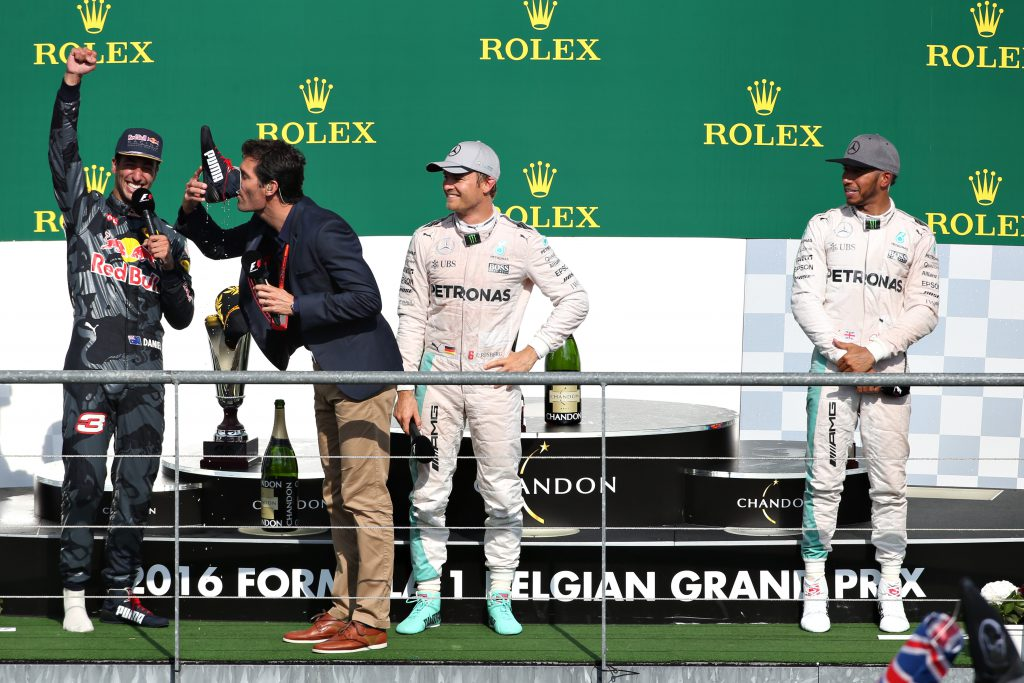 SPA, BELGIUM - AUGUST 28: Mark Webber drinks champagne from the boot of Daniel Ricciardo of Australia and Red Bull Racing on the podium during the Formula One Grand Prix of Belgium at Circuit de Spa-Francorchamps on August 28, 2016 in Spa, Belgium (Photo by Charles Coates/Getty Images)